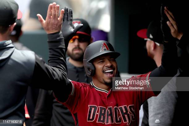 Eduardo Escobar of the Arizona Diamondbacks celebrates in the dugout after hitting a solo home run against the Colorado Rockies in the second inning...