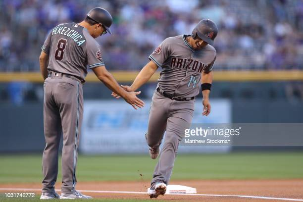 Eduardo Escobar of the Arizona Diamondbacks is congratulated by third base coach Tony Perezchica as he circles the bases to score on a David Peralta...