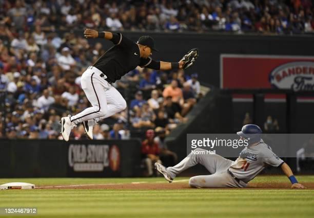 Eduardo Escobar of the Arizona Diamondbacks makes a leaping catch on a wild throw from Christian Walker as AJ Pollock of the Los Angeles Dodgers...