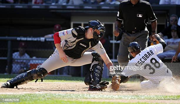 Eduardo Escobar of the Chicago White Sox slides safely into home plate avoiding the tag of Chris Snyder of the Houston Astros on June 9 2012 at US...