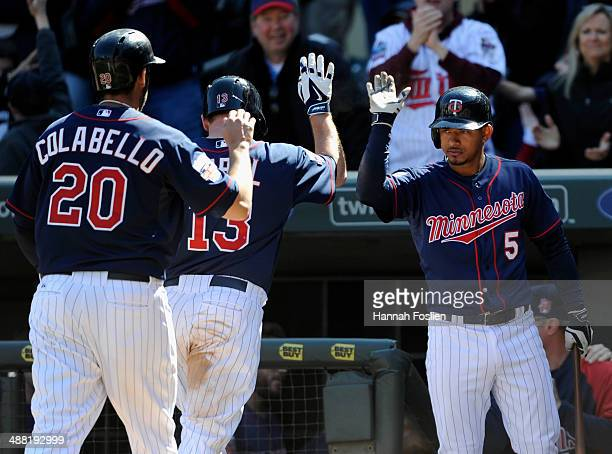 Eduardo Escobar of the Minnesota Twins congratulates teammate Chris Colabello and Jason Kubel of the Minnesota Twins on scoring against the Baltimore...