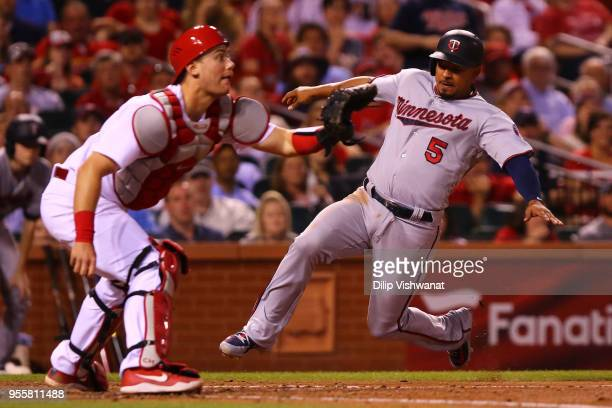 Eduardo Escobar of the Minnesota Twins scores a run against Carson Kelly of the St Louis Cardinals in the fourth inning at Busch Stadium on May 7...