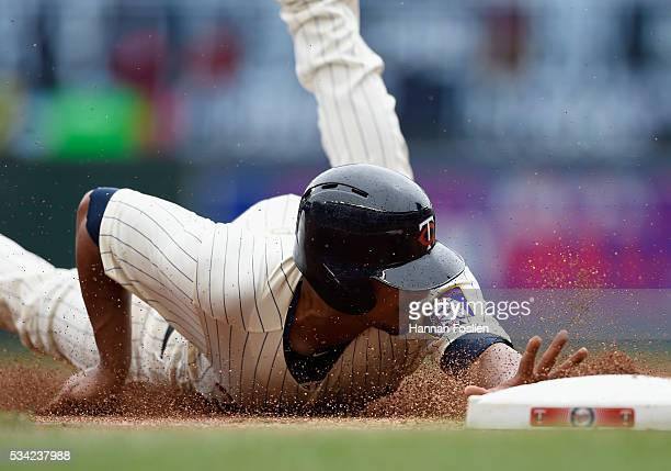 Eduardo Escobar of the Minnesota Twins slides safely into third base after a throwing error on a pickoff attempt at first base by Dillon Gee of the...