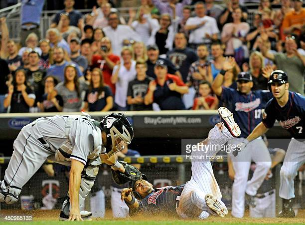 Eduardo Escobar of the Minnesota Twins slides safely to score the winning run as Adrian Nieto of the Chicago White Sox defends home plate during the...