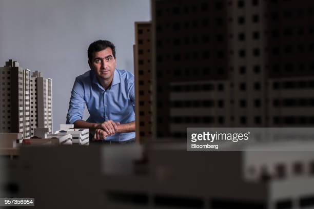Eduardo Fischer, co-chief executive officer of MRV Engenharia e Participacoes SA, stands for a photograph in front of a model of the Reserva Paulista...