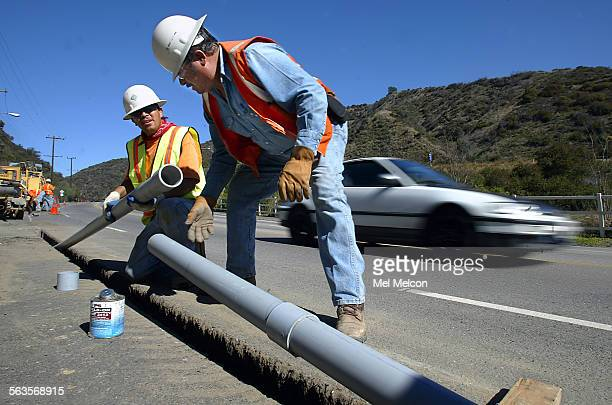 Eduardo Gonzalez left and Sam Alvarado install pvc pipe into trenches cut out along Sepelveda Blvd north of Getty Center Dr in Brentwood Fiber optic...