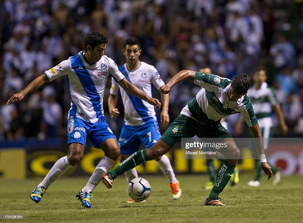 Eduardo Herrera of Santos competes for the ball with Luis Noriega of Puebla during a match between Puebla and Santos as part of the Torneo de Apertura 2013 Liga MX Championship at Cuauhtemoc Stadium, on July 31, 2013 in Puebla, Mexico.