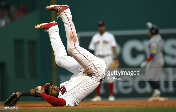 Eduardo Nunez of the Boston Red Sox attempts to throw the ball to first as he falls in the eighth inning on a ball hit by Jesus Sucre of the Tampa...