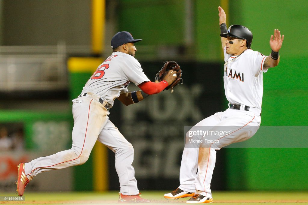 Eduardo Nunez #36 of the Boston Red Sox chases down Derek Dietrich #32 of the Miami Marlins in the thirteenth inning at Marlins Park on April 3, 2018 in Miami, Florida.