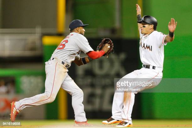 Eduardo Nunez of the Boston Red Sox chases down Derek Dietrich of the Miami Marlins in the thirteenth inning at Marlins Park on April 3, 2018 in...