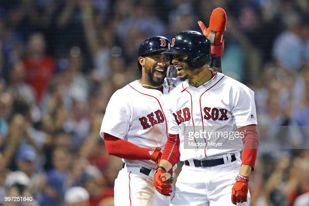 Eduardo Nunez of the Boston Red Sox congratulates Mookie Betts after he hit a grand slam against the Toronto Blue Jays during the fourth inning at...