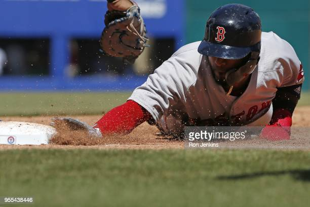 Eduardo Nunez of the Boston Red Sox dives safely back to first base avoiding the tag by Ronald Guzman of the Texas Rangers during the sixth inning at...