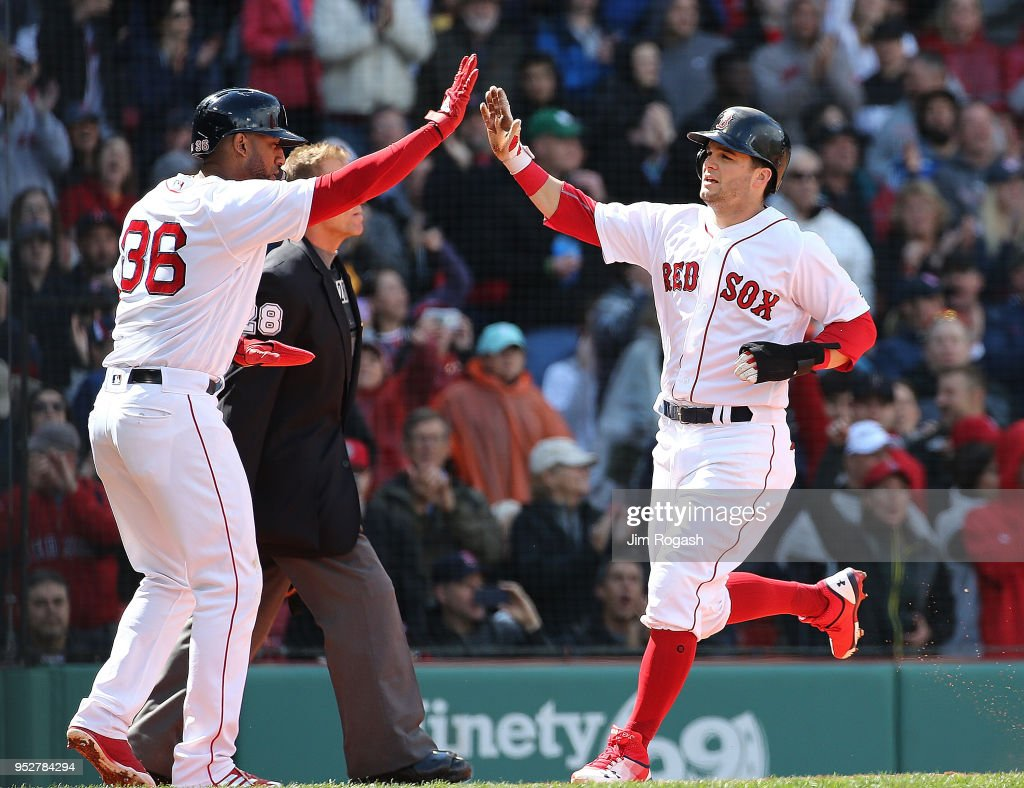 Eduardo Nunez #36 of the Boston Red Sox greets Andrew Benintendi #16 after they scored on a hit by J.D. Martinez #28 in the sixth inning against the Tampa Bay Rays at Fenway Park on April 29, 2018 in Boston, Massachusetts.