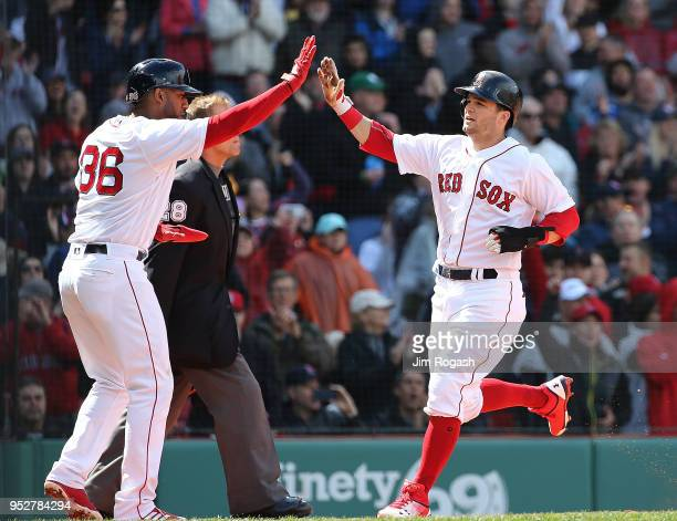 Eduardo Nunez of the Boston Red Sox greets Andrew Benintendi after they scored on a hit by J.D. Martinez in the sixth inning against the Tampa Bay...