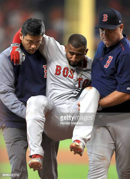Eduardo Nunez of the Boston Red Sox is carried off the field by Red Sox trainer Masai Takahashi and manager John Farrell after suffering an injury in...
