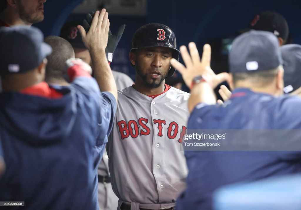 Eduardo Nunez #36 of the Boston Red Sox is congratulated by teammates in the dugout after scoring a run in the seventh inning during MLB game action against the Toronto Blue Jays at Rogers Centre on August 28, 2017 in Toronto, Canada.
