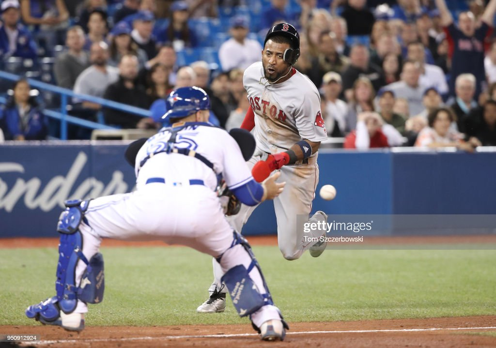 Eduardo Nunez #36 of the Boston Red Sox is thrown out at home plate in the ninth inning during MLB game action as Russell Martin #55 of the Toronto Blue Jays waits for the throw at Rogers Centre on April 24, 2018 in Toronto, Canada.