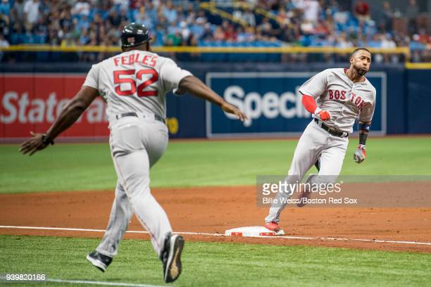 Eduardo Nunez of the Boston Red Sox is waved home by third base coach Carlos Febles as he hits an inside the park home run during the second inning...