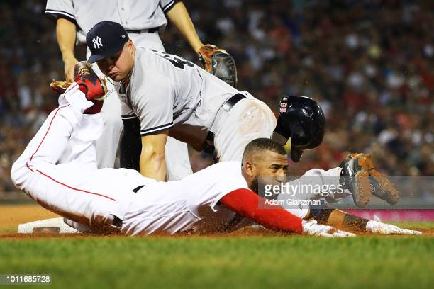 Eduardo Nunez of the Boston Red Sox slides safely into first base under the diving tag of Luke Voit of the New York Yankees at Fenway Park on August...