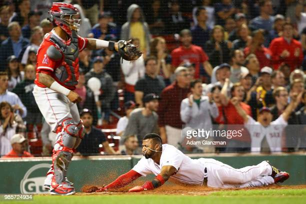 Eduardo Nunez of the Boston Red Sox slides safely into home plate past Martin Maldonado of the Los Angeles Angels in the seventh inning a game at...