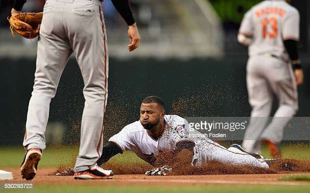 Eduardo Nunez of the Minnesota Twins slides safely into third base against Ryan Flaherty of the Baltimore Orioles during the first inning of the game...