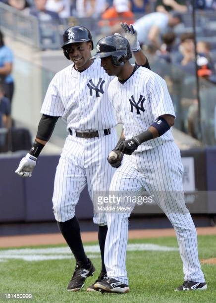 Eduardo Nunez of the New York Yankees celebrates with his teammate Curtis Granderson after hitting a tworun homer during the fourth inning against...