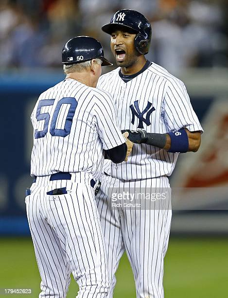 Eduardo Nunez of the New York Yankees reacts with first base coach Mick Kelleher after Nunez hit a double to knock in two runs to break a 44 tie...