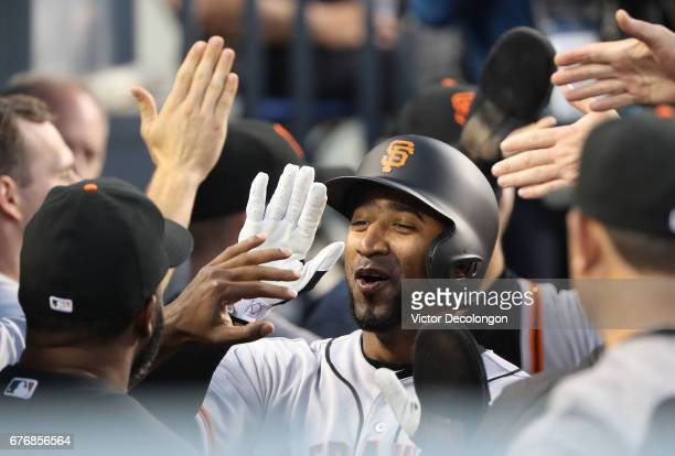 Eduardo Nunez of the San Francisco Giants celebrates with teammates in the dugout after scoring in the second inning on a single to center by...