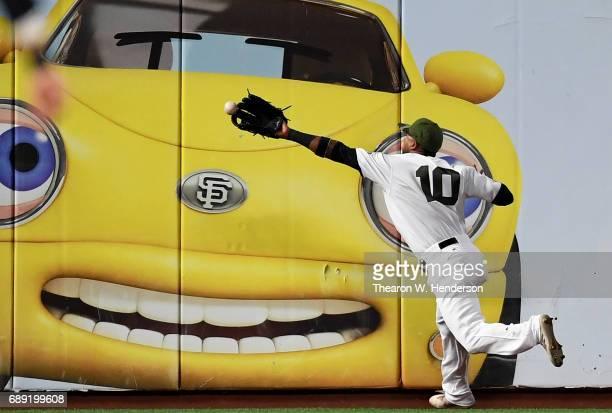 Eduardo Nunez of the San Francisco Giants crashes into the wall as the ball goes off his glove for a double off the bat of Rio Ruiz of the Atlanta...