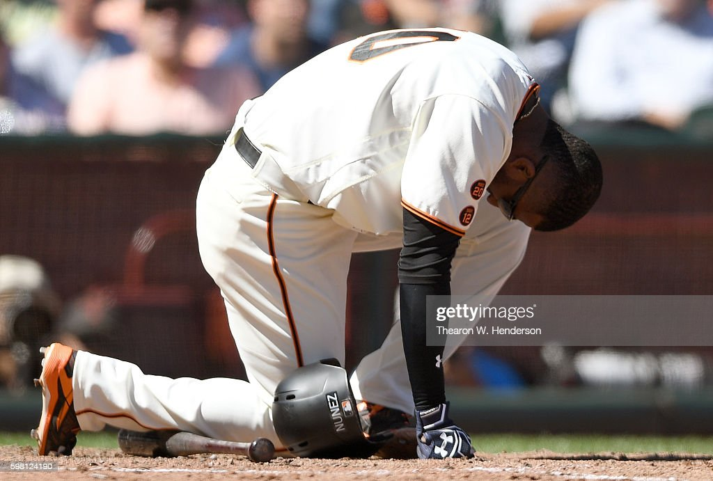 Eduardo Nunez #10 of the San Francisco Giants goes to one knee after he was hit by a pitch from Shelby Miller #26 of the Arizona Diamondbacks in the bottom of the six inning at AT&T Park on August 31, 2016 in San Francisco, California.