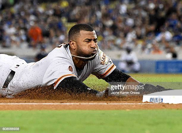 Eduardo Nunez of the San Francisco Giants reaches third on a throwing error by Yasmani Grandal of the Los Angeles Dodgers in the third inning of the...