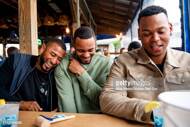 Eduardo Nunez Xander Bogaerts and Rafael Devers of the Boston Red Sox react as they eat crabs during a visit to Nick's Fish House on May 8 2019 in...