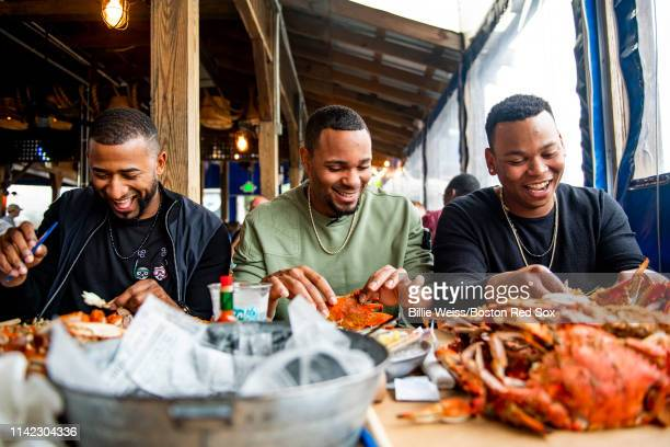 Eduardo Nunez Xander Bogaerts and Rafael Devers of the Boston Red Sox eat crabs during a visit to Nick's Fish House on May 8 2019 in Baltimore...