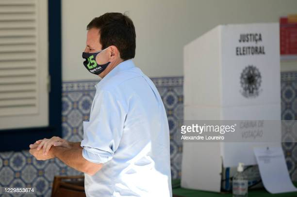 Eduardo Paes, candidate for mayor of the city of Rio de Janeiro for the Democratic Party cleans his hands after voting in Sao Conrado neighborhood on...