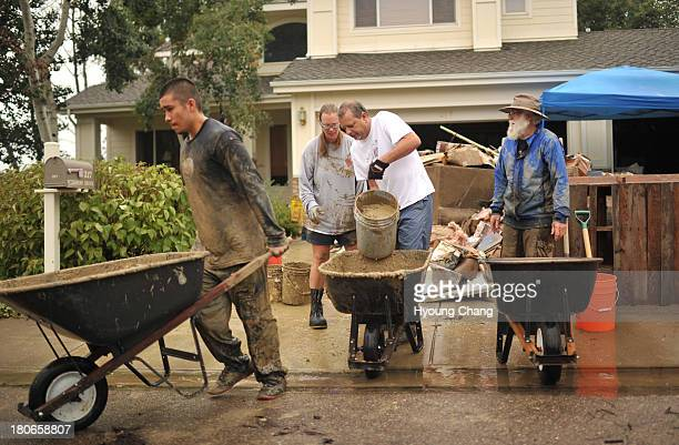 Eduardo Palomares left and neighbors of Stan McDonald are moving the mud out from the basement of McDonald's house damaged by flooding near the...