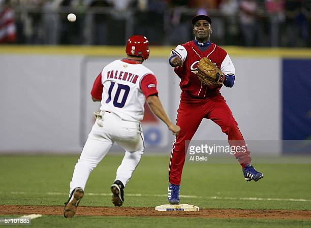 Eduardo Paret of Cuba throws to complete a double play to end the eighth inning as Jose Valentin of Puerto Rico looks to slide during Round 2 of the...