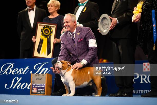 Eduardo Paris a native of Peru poses for a group photo as his Bulldog named Thor wins the Best in Show at the Greater Philadelphia Expo Center on...