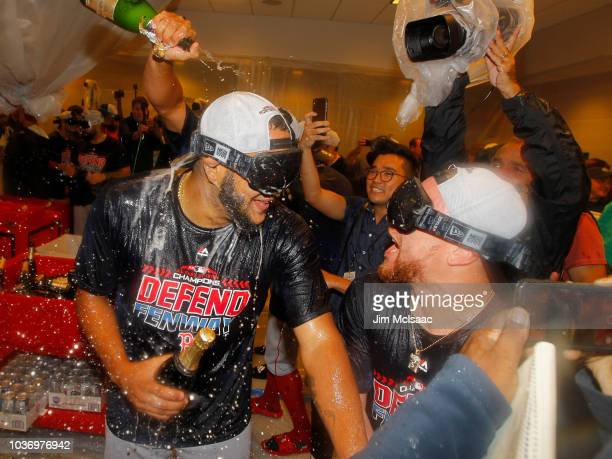 Eduardo Rodriguez and Christian Vazquez of the Boston Red Sox celebrate in the locker room with his teammates after defeating the New York Yankees to...
