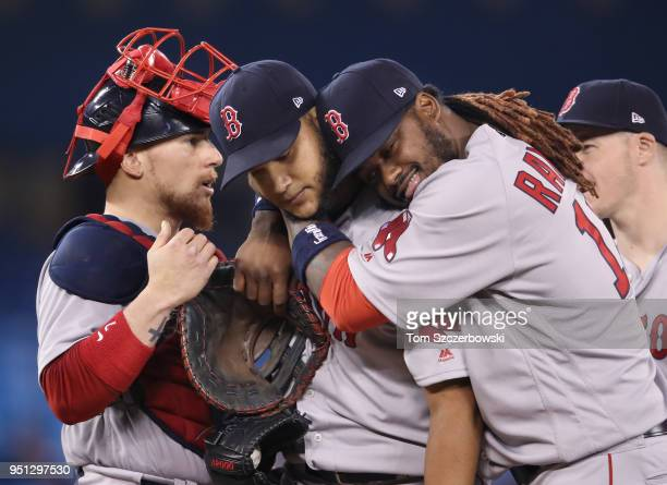 Eduardo Rodriguez of the Boston Red Sox waits on the mound to be relieved as he is congratulated by Hanley Ramirez in the seventh inning during MLB...