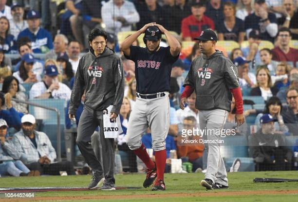 Eduardo Rodriguez of the Boston Red Sox walks with a Red Sox trainer and manager Alex Cora to first base after being hit by a pitch on his right arm...