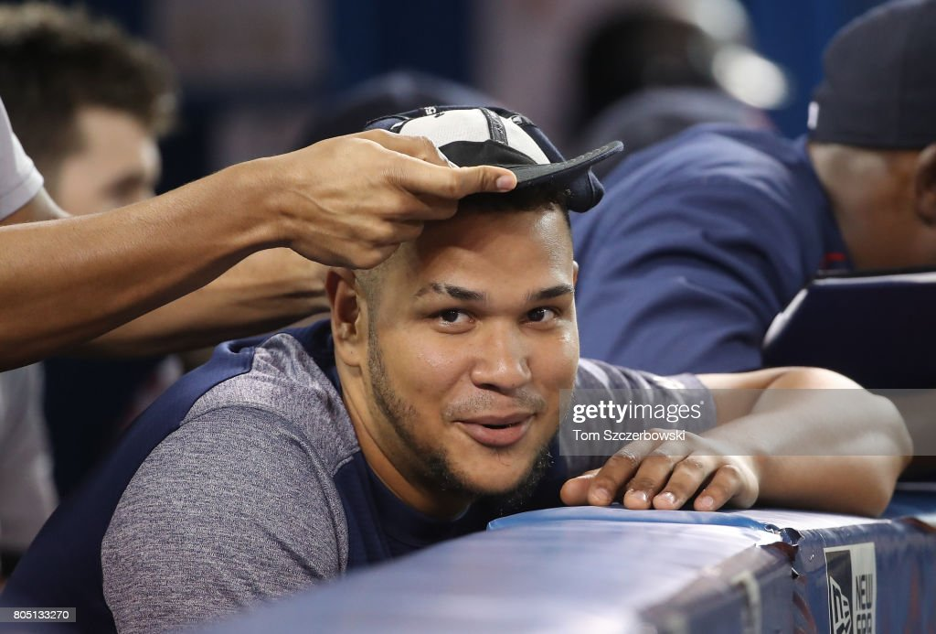 Eduardo Rodriguez #52 of the Boston Red Sox watches as Xander Bogaerts #2 turns his cap inside-out into a rally hat in the sixth inning during MLB game action against the Toronto Blue Jays at Rogers Centre on June 30, 2017 in Toronto, Canada.