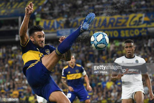 Eduardo Salvio of Boca Juniors kicks the ball against Harrinson Mancilla of Gimnasia y Esgrima during a match between Boca Juniors and Gimnasia y...
