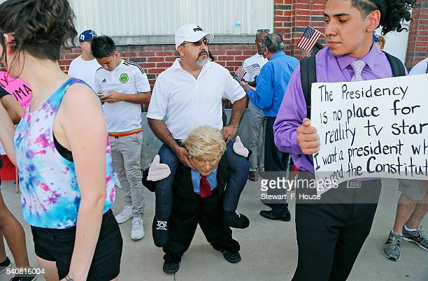 Eduardo Tamayo of Cedar Hill Texas wears a costume to make it appear as if he is riding on Donald Trump's back outside a rally for the presumptive...