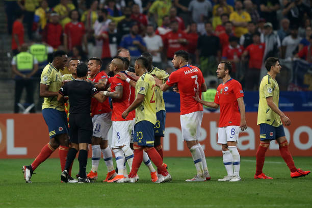 Eduardo Vargas and Arturo Vidal of Chile and Roger Martinez of Colombia argue with Hernan Maidana assistant referee during the Copa America Brazil...