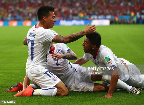 Eduardo Vargas of Chile celebrates scoring his team's first goal with Eugenio Mena and Gonzalo Jara during the 2014 FIFA World Cup Brazil Group B...