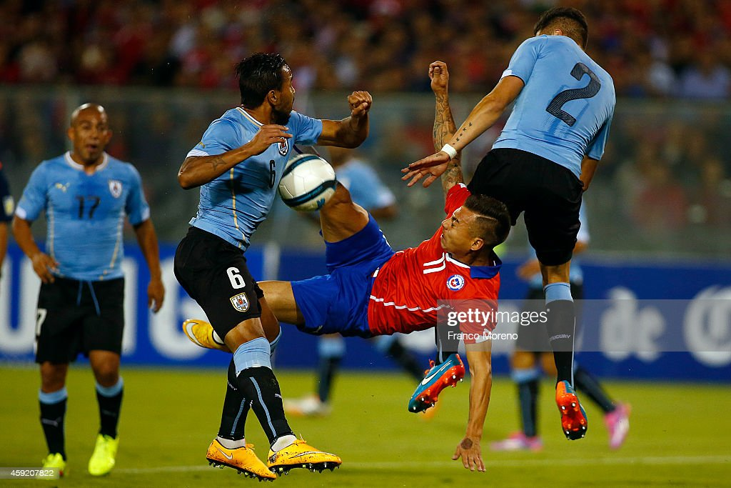 Eduardo Vargas of Chile (C) fights for the ball with Alvaro Pereira of Uruguay (L) during an international friendly match between Chile and Uruguay at Monumental Stadium on November 18 2014 in Santiago, Chile.