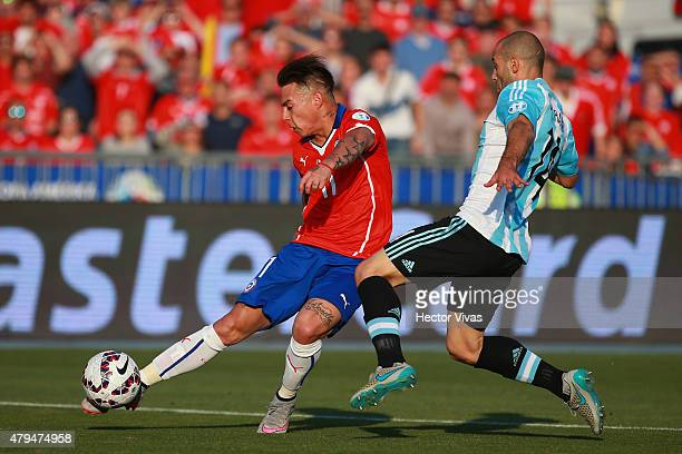 Eduardo Vargas of Chile kicks the ball while Javier Mascherano of Argentina tries to stop him during the 2015 Copa America Chile Final match between...