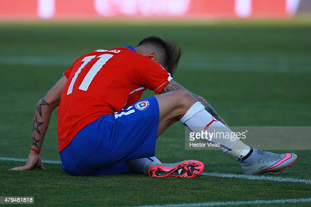 Eduardo Vargas of Chile lies injuried during the 2015 Copa America Chile Final match between Chile and Argentina at Nacional Stadium on July 04 2015...