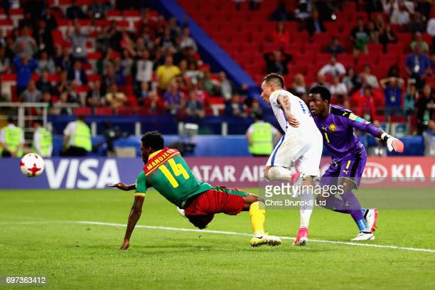 Eduardo Vargas of Chile puts the ball past Fabrice Ondoa of Cameroon and Georges Mandjeck of Cameroon to score the second goal for Chile during the...
