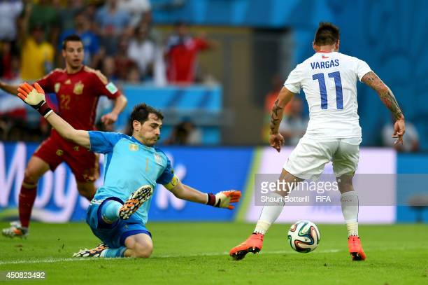 Eduardo Vargas of Chile scores the team's first goal past Iker Casillas of Spain during the 2014 FIFA World Cup Brazil Group B match between Spain...